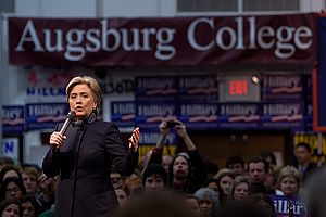 "Clinton speaking at a college rally as part of her 2008 Presidential campaign, with a crowd behind her looking on. She is speaking at Augsburg College in Minneapolis, two days before ""Super Tuesday"", the day in 2008 when the largest number of simultaneous state-level elections was held. She is wearing a black suit. There are blue banners with the word ""Hillary"" on them, hung around the room, as well as a large white-on-burgundy banner with the words ""Augsburg College""."