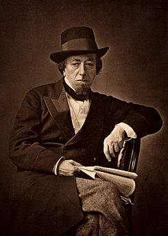 Disraeli in old age, wearing a double-breasted suit, bow tie and hat