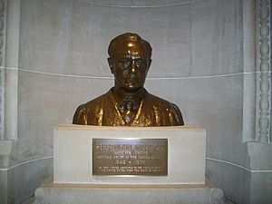 A shining bronze bust of an expressionless man sitting on a pedestal.