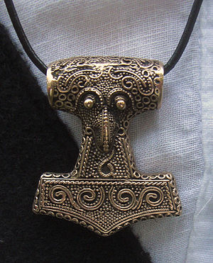 A metal hammer, worn as a pendant around an individual's neck