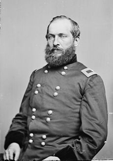 Seated portrait in army uniform. Garfield has a full beard and mustache