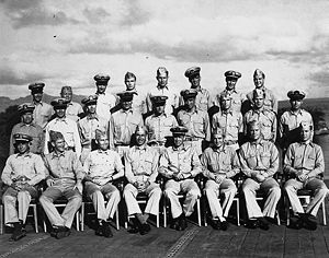 Twenty-eight Sailors in the uniform of the United States Navy pose on the deck of a World War II-era Aircraft Carrier.