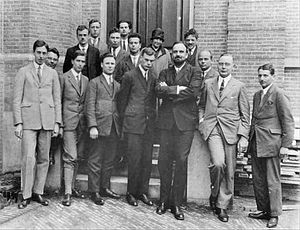 Fifteen men in suits, and one woman, pose for a group photograph