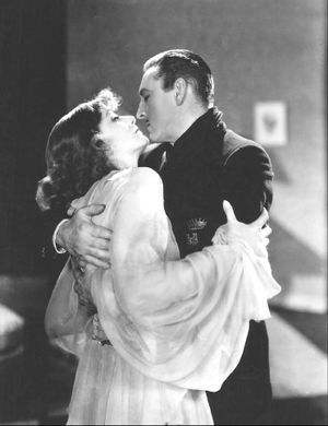 Greta Garbo and Barrymore standing, in a close embace, about to kiss
