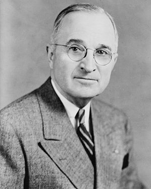 Half length portrait of a man wearing suit and tie with his head turned to looking directly forward; He has a slight smile on his face, with a receding hairline and large round glasses