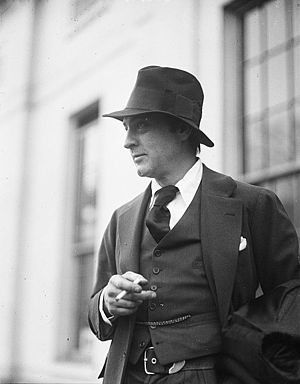 Picture of Barrymore outside, from the waist up, pensively smoking a cigarette and facing to the left