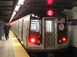 The back end of a subway train, with a red E on a LED display on the top. To the left of the train is a platform with a person walking away.