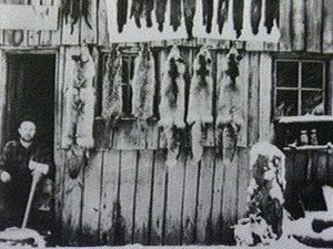Man by wooden building that has six fur pelts on it.