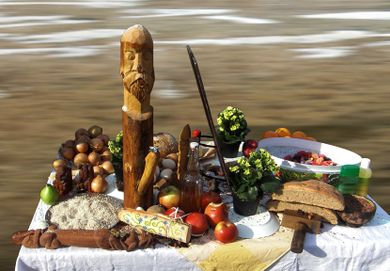 A table on which fruits and some wooden icons are situated.