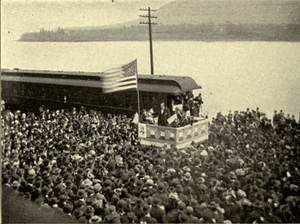 A dramatic political scene. Beside a river stands a podium, on which a flagpole flies a huge American flag. Beneath the flag stands a candidate in a dark suit addressing an impressive crowd which takes up most of the photograph. Not only the quayside, but a ferry beside it on the water are packed full of people listening intently.