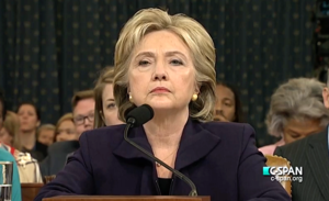 Clinton testifying before the House Select Committee on Benghazi on October 22, 2015. She is standing behind a podium with a microphone, with many people behind her.