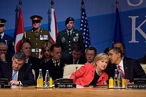 Obama whispering to Clinton at a summit meeting, with multiple soldiers in uniform standing behind them and heads of state sitting behind and in front of them. They are in the 21st NATO summit, which was held in April 2009.