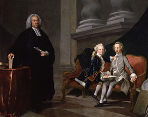 Conversation piece in oils: Ayscough dressed in black with a clerical collar stands beside a settee on which the two boys sit, one wearing a grey suit the other a blue one. He holds a sheet of paper; the boys hold a book.