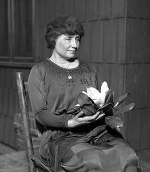 A woman with full dark hair and wearing a long dark dress, her face in partial profile, sits in a simple wooden chair. A locket hangs from a slender chain around her neck; in her hands is a magnolia, its large white flower surrounded by dark leaves.