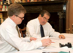 Two men in shirtsleeves work at a table, there are quantities of paper in front of them..