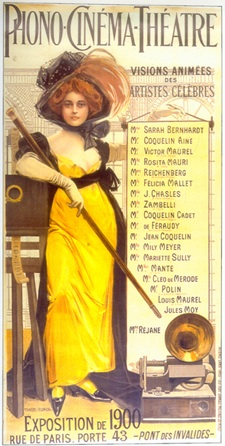 "Illustration of a red-haired woman wearing a large hat, an ankle-length yellow dress, and high heels. She is holding a long baton or swagger stick and leaning against a film projector. A gramophone sits at her feet. The top of the illustration reads ""Phono-Cinéma-Théâtre"". Text to the left of the woman reads ""Visions Animées des Artistes Celèbres"", followed by a list of performers."