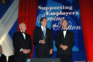 Photograph of Romney flanked by two other men at a formal awards occasion
