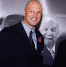 A bald man in a black suit posing in front of an earlier picture of himself.