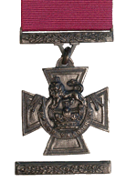A bronze cross pattée bearing the crown of Saint Edward surmounted by a lion with the inscription FOR VALOUR. A crimson ribbon is attached
