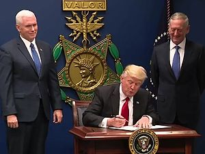 Donald Trump signing the order with Mike Pence and James Mattis at his side