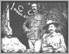 Photograph of three men at a boy scout event circa 1910.  The man seated on the left is unidentified, Burnham is in the middle, standing, and Baden-Powell is on the right, seated.  There is a table in front of the men.  Baden-Powell is wearing his stetson hat, Burnham has no hat, and man on the left has a modest hat.  Behind Burnham and to his right is a flag partially opened.