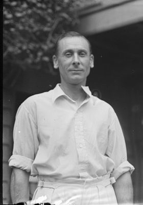 A man standing wearing cricket whites