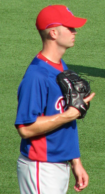 A man in a blue baseball jersey, gray baseball pants, and a red baseball cap stands on a green field. He has a black baseball glove on his right hand.