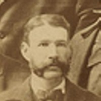 A man in a suit with a mutton-chop mustache.