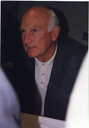 An older, largely bald man with white hair in a blue jacket and white shirt sits while looking up at a person out of frame to the left.