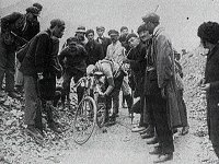 Black and white image of man bending over his bicycle while several other men are watching.