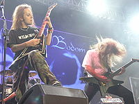 A color photograph of two members of the group Children of Bodom standing on a stage with guitars, drums are visible in the background