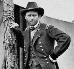 Photograph of Grant in uniform leaning on a post in front of a tent