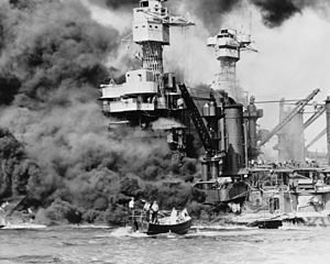 Dark smoke billows from the ship after the Pearl Harbor attack while a man is rescued from the water by sailors in a small boat