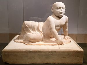 Beige marble statue of a stout young child aged about two years old lying on his left side. The child's head is shaved, his eyes gaze over the viewer's shoulder and his lower body is covered in a draping cloth that hangs limply between his flexed feet. The child supports his torso with his left hand in which he holds an unidentifiable object, he also holds a small bird in his right hand. The sculpture rests on a heavy socle inscribed with barely visible letters spanning the upper part of the socle vertically.