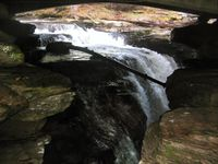 The upper half of a falls dropping into a narrow slot in layered rock, as seen from the side. The curved underside of a bridge is visible above the waterfall, which is in shadow.