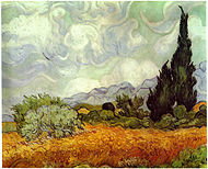 An open field of yellow wheat, under swirling and bright white clouds in an afternoon sky. A large cypress tree to the extreme right painted in shades of dark greens with swirling and impastoed brushstrokes. There are several smaller trees to the left and around the cypress tree are more small trees and several haystacks. There are blue-gray hills on the horizon in the background