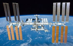 A rearward view of the International Space Station backdropped by the limb of the Earth. In view are the station's four large, gold-coloured solar array wings, two on either side of the station, mounted to a central truss structure. Further along the truss are six large, white radiators, three next to each pair of arrays. In between the solar arrays and radiators is a cluster of pressurised modules arranged in an elongated T shape, also attached to the truss. A set of blue solar arrays are mounted to the module at the aft end of the cluster.