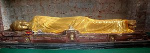 Gold colored statue of Buddha reclining on his right side