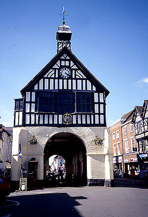 A photograph of a building on a clear summer's day, with a white stone base and a black and white timbered first floor. An archway leads through the middle of the building, apparently located in the middle of a small town.