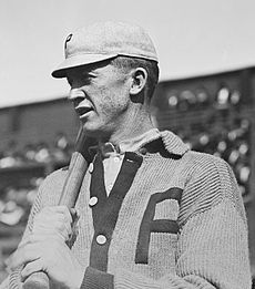 "A man in a baseball cap and V-neck buttoned sweater looks to the left of the image. His sweater and his hat both display the letter ""P"" in block type, and he holds a baseball bat over his shoulder with both hands."
