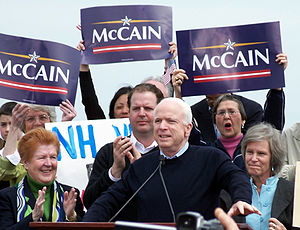 "White-haired man speaking at podium, with group of people behind him, some holding blue ""McCain"" signs"