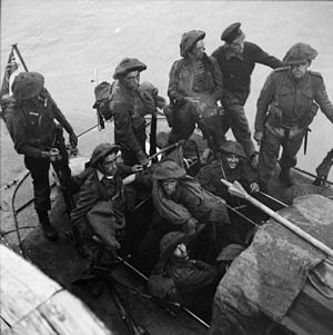 A black and white photograph showing soldiers wearing combat equipment sitting in a small watercraft beside a pier