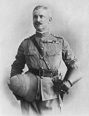 Mustached man in officers uniform. With San-Browne belt, sword at waist, wearing gauntlets and holding his pith helmet at waist level in his right hand.