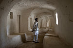 A picture of a man standing in the middle of a hallway made of limestone.