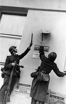 Photo of two German soldiers removing Polish government insignia from a wall.
