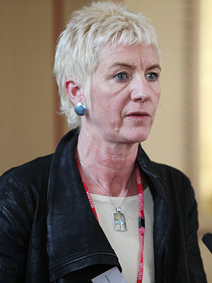 Middle-aged woman with short, very-light hair speaking into a microphone.
