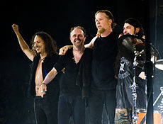 Four men in dark clothing on a stage; the man on the left has his arm raised in the air, while the third man from the left has his arms around the second and fourth.