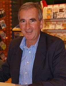 A photograph of a man in his fifties looking at the camera. He is wearing an open-collared blue shirt and a blue jacket.