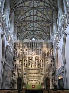The photo shows the altar of St. Alban's Cathedral, behind which rises a large stone screen with tiers of statues, and a crucifix, centrally placed.