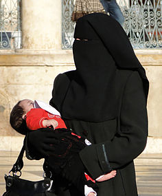 Woman wearing a niqab with baby